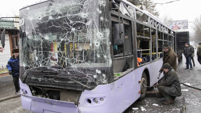 People surround a damaged trolleybus in Donetsk, January 22, 2015. At least six civilians were killed on Thursday when a shell or a mortar hit a trolleybus stop in the rebel-controlled city of Donetsk in eastern Ukraine, a Reuters witness said. The Reuters cameraman said he saw six bodies on the ground near, and inside, a trolleybus in a southern district of the city. Windows of shops nearby had been blown out by the blast. REUTERS/Alexander Ermochenko (UKRAINE - Tags: DISASTER CIVIL UNREST CONFLICT TRANSPORT)