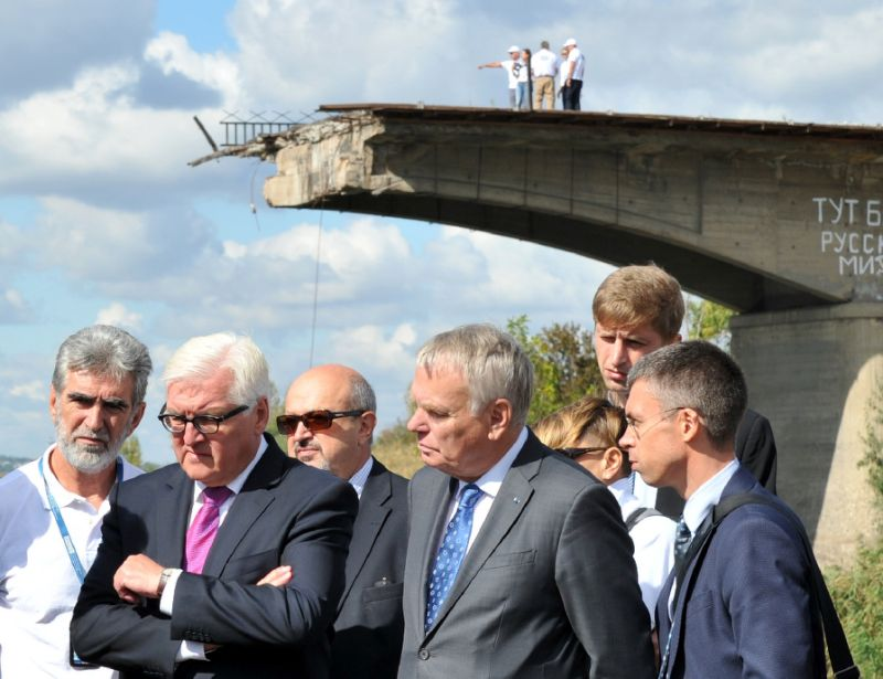 German Foreign Minister Frank-Walter Steinmeier (2nd left) and his French counterpart Jean-Marc Ayrault (3rd right) stand in front of a destroyed bridge during a visit in Slavyansk, eastern Ukraine, on September 15, 2016 (AFP Photo/Sergey Bobok)