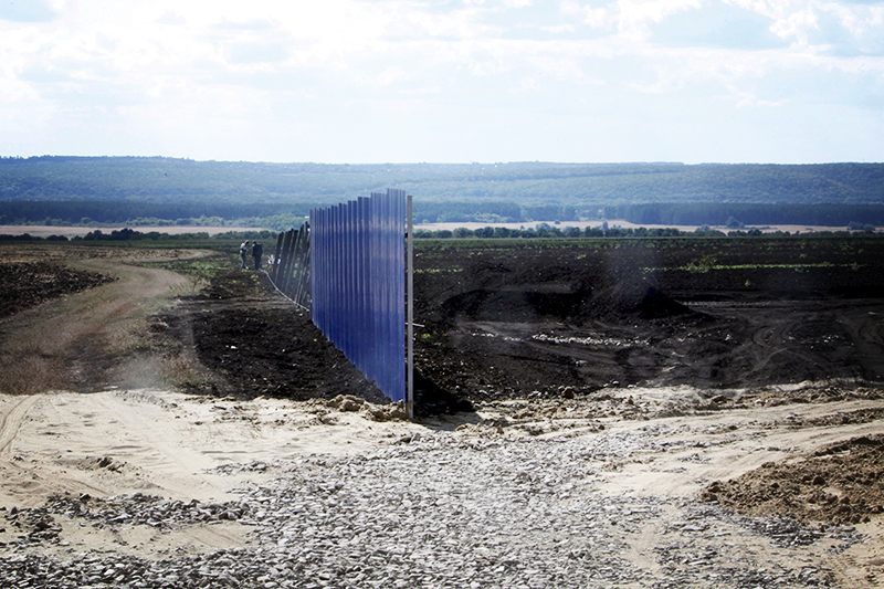 Workers install a fence at a construction site for Russia's new military base near the Russian-Ukrainian border in the village of Soloti, southeast of Belgorod, Russia, September 7, 2015. Russia has started to build a huge military base housing ammunition depots and barracks for several thousand soldiers near the Ukrainian border, a project that suggests the Kremlin is digging in for a prolonged stand-off with Kiev. The base, when completed, will even have its own swimming pool, skating rink and barber shop, according to public documents. Picture taken September 7, 2015. REUTERS/Anton Zverev - RTSCKZ