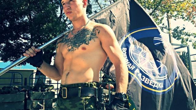 Фотографія Раменського з прапором воєнної розвідки і неонацистським татуюванням