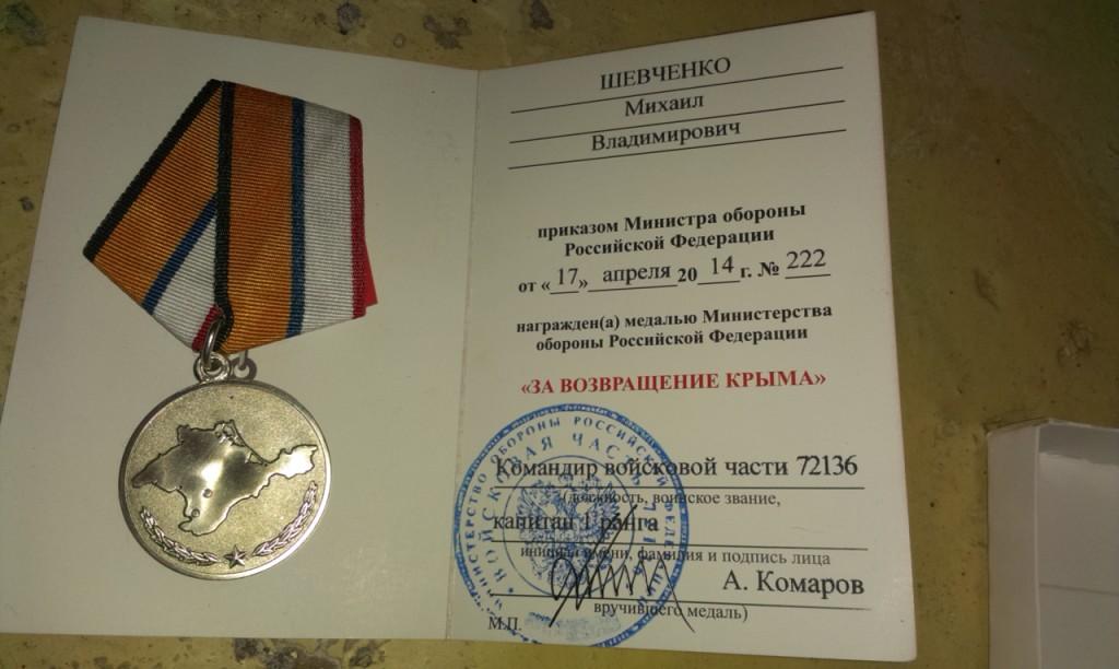 Mikhail Sjevtjenko visar upp med en medalj