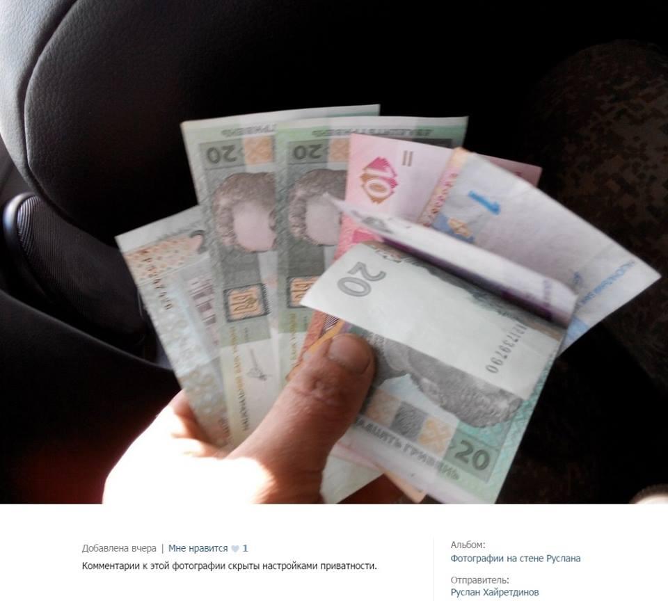 Оккупант демонстрирует украинские деньги