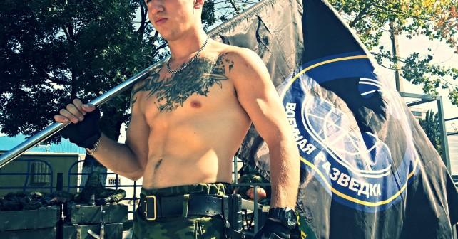 Фотогарфия Раменского с флагом военной разведки РФ и нео-нацисткой татуировкой