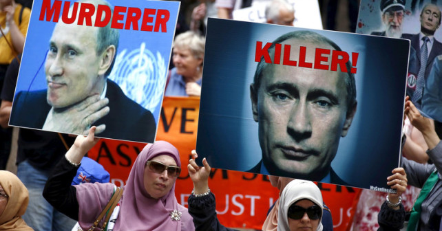 Members of the Syrian and Palestinian communities hold aloft placards displaying pictures of Russian President Vladimir Putin during a rally in support of refugees that was part of a national campaign in central Sydney, Australia, October 11, 2015. The crowd, estimated at around one thousand people, called for an end to mandatory detention for refugees and for an end to Russia's intervention in Syria. REUTERS/David Gray